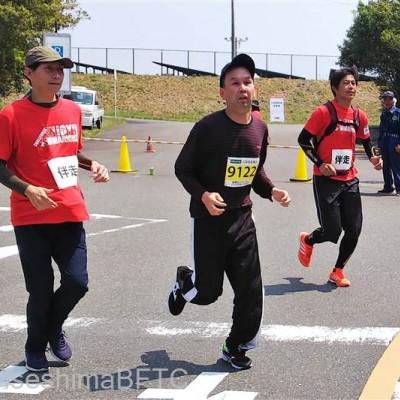 全速力で走る選手と、両脇でサポートするボランティア2名
